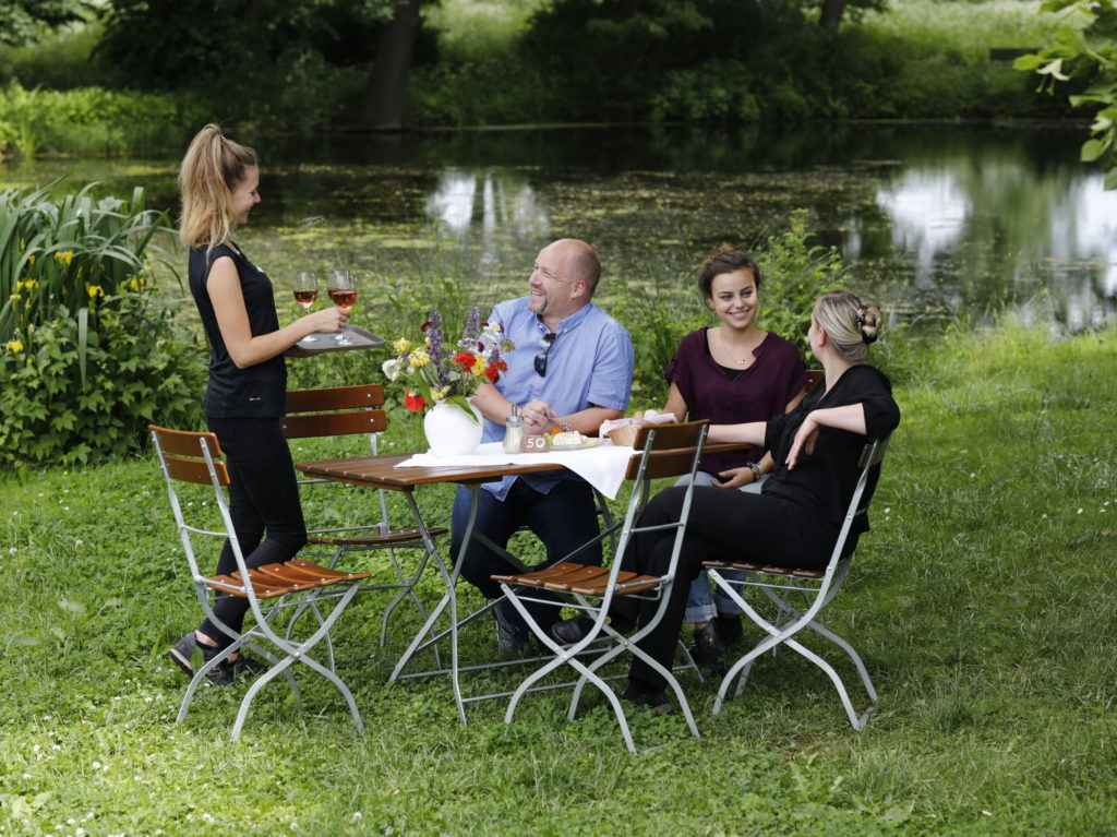 People at the table in front of a pond