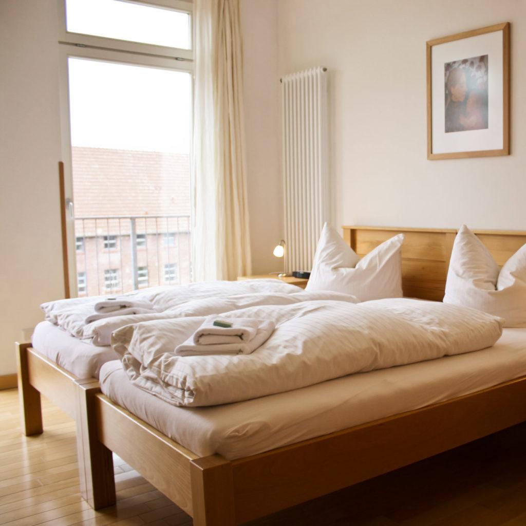 Doppelbett mit bodentiefem Fenster