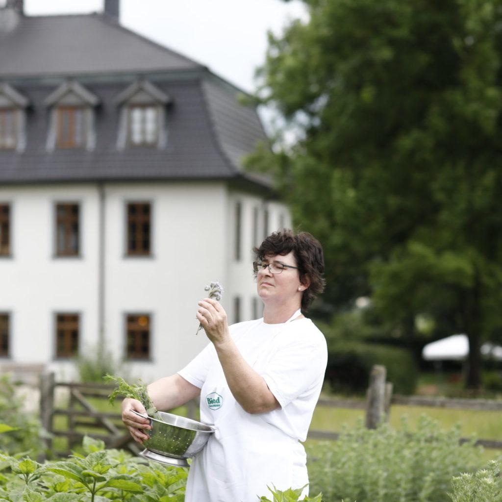 Frau im Kräutergarten mit Kräutern