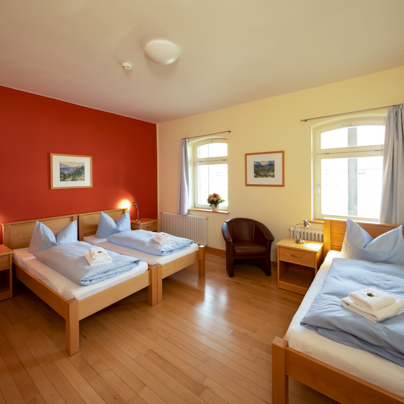 Dreibettzimmer mit zwei Fenstern